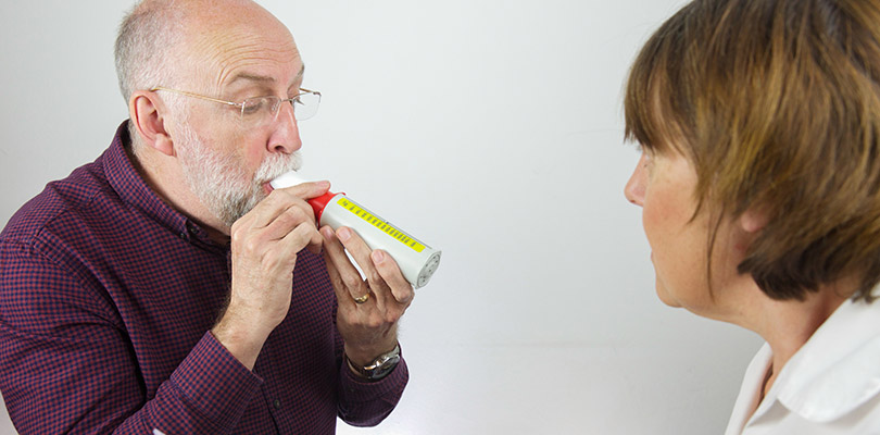 A man is using a peak flow meter while a doctor observes