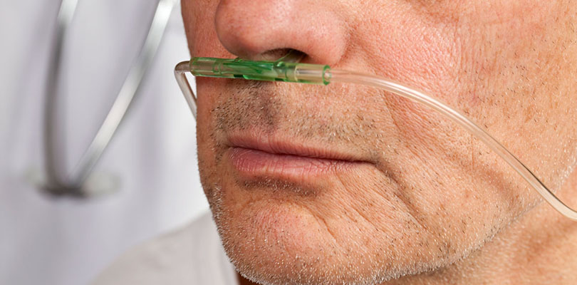A man at end-stage COPD is using an oxygen machine