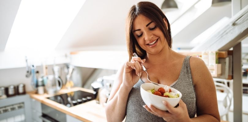 Someone eating foods to avoid bloating.