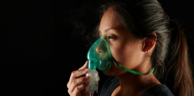 Someone breathing with an oxygen mask.