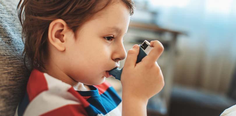 A little boy sitting on a couch using an inhaler.