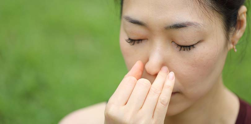 Someone using the interchanging nostril breathing technique outside.