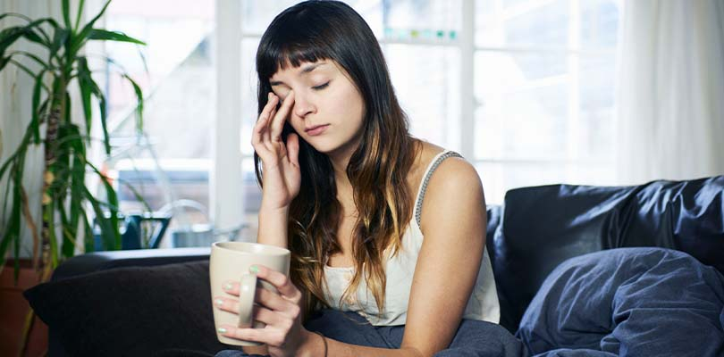 A woman sitting in bed with a cup of coffee rubbing her eyes.