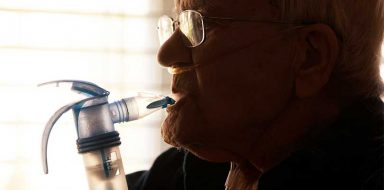 A older person breathing into a breathing device.