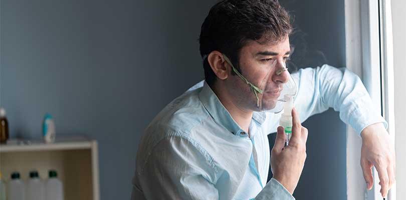 A man breathing through an oxygen mask.