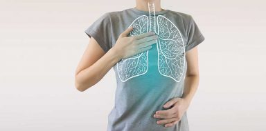 A person wearing a grey t-shirt with an outline of lungs holding their chest and stomach.