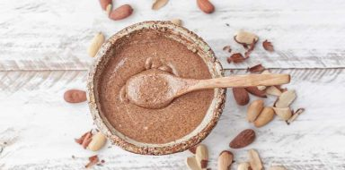 A jar full of almond butter with a wooden spoon in it.